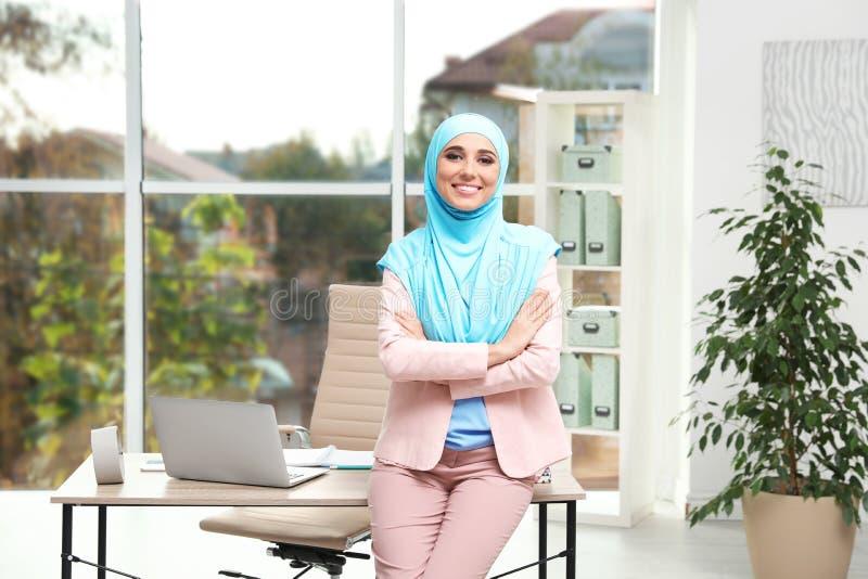 Moderne Moslimonderneemster die hijab dichtbij lijst dragen stock foto's