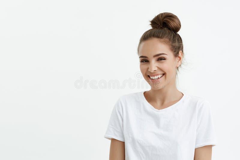 Moderne nette europäische Frau mit Brötchen breit lächelnd und auf Kamera bei der Stellung flüchtig blickend über weißem Hintergr lizenzfreies stockbild