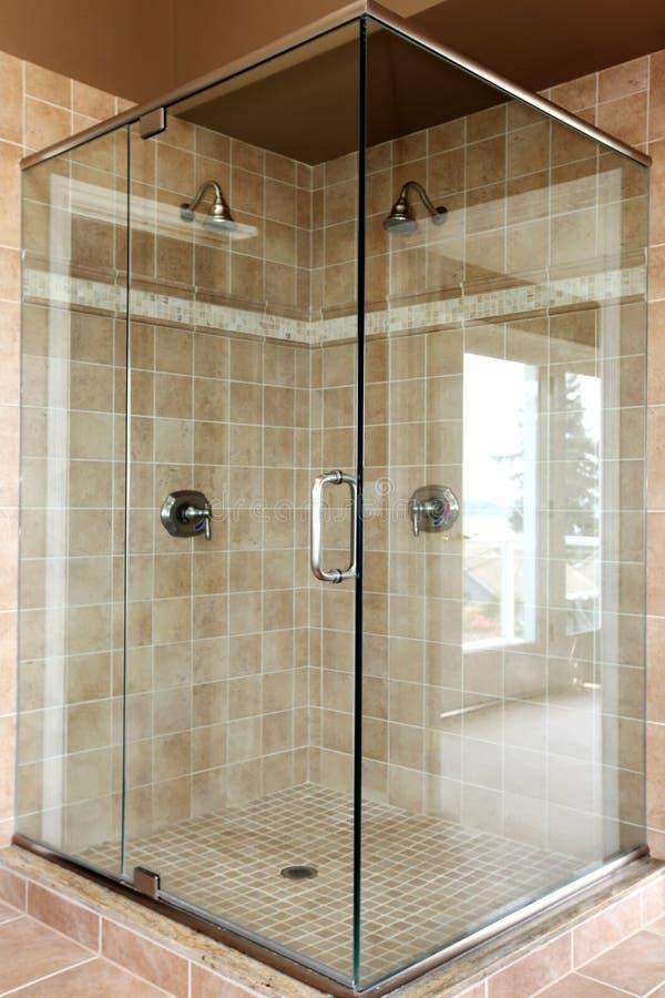 Moderne nieuwe glasgang in douche met beige tegels. royalty-vrije stock afbeelding