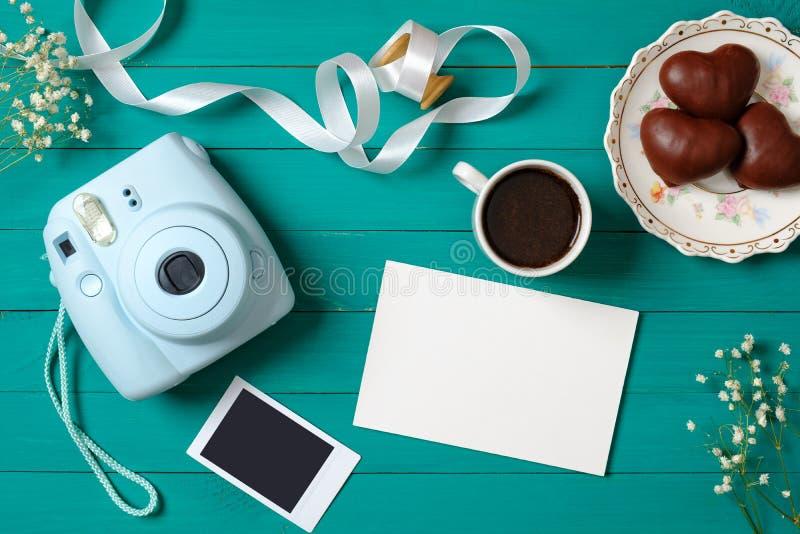 Moderne onmiddellijke camera, kop van koffie, onmiddellijk fotobeeld, tedere bloemen op groene houten achtergrond De hoogste meni royalty-vrije stock afbeelding