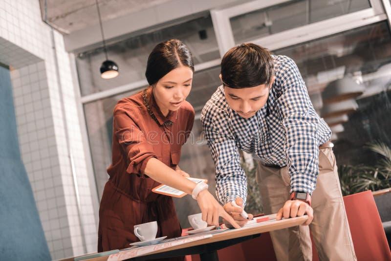 Moderne Paare von den Freiberuflern, welche die intelligenten Uhren haben Diskussion tragen lizenzfreies stockfoto