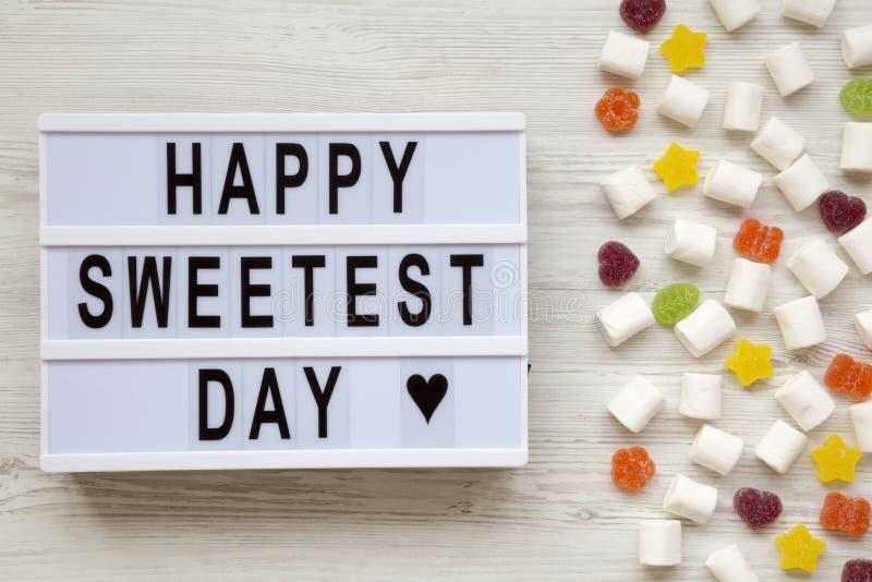 Moderne raad met Gelukkig Zoetste de Dag` woord van ` en suikergoed op een witte houten achtergrond, luchtmening De hoogste vlakk royalty-vrije stock foto