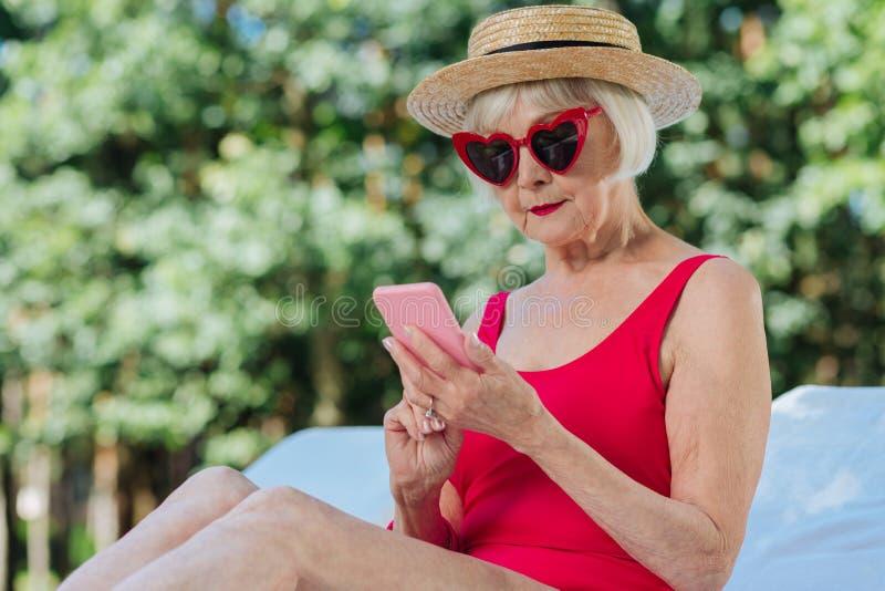 Moderne rijpe vrouw die haar roze slimme telefoon in handen houden royalty-vrije stock afbeelding