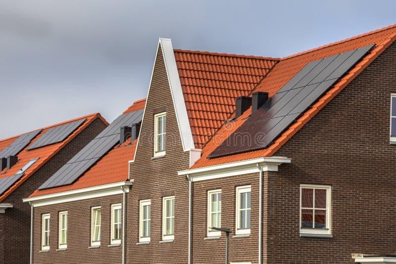 Moderne rijtjeshuizen met rode daktegels en zonnepanelen stock foto's