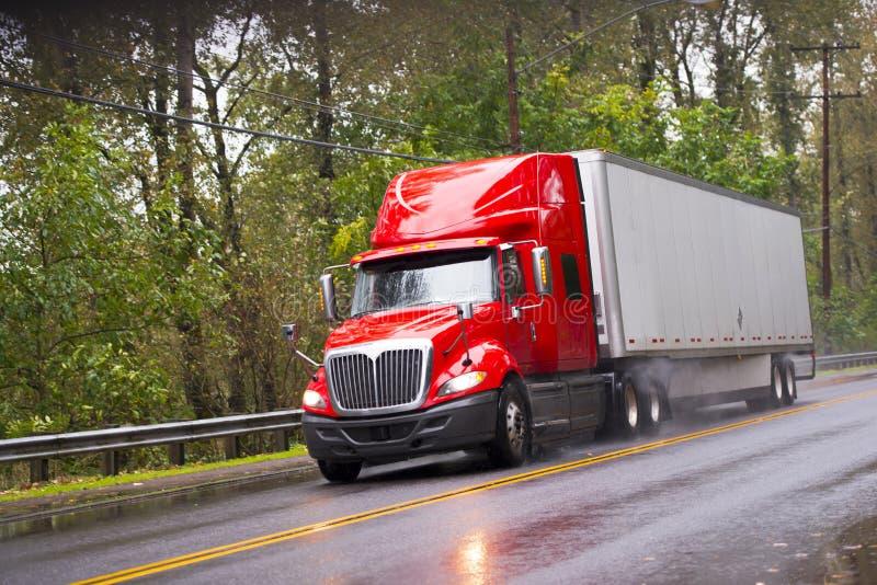 Moderne rode glanzend in aanhangwagen van de regen de semi vrachtwagen op regenende weg stock afbeelding