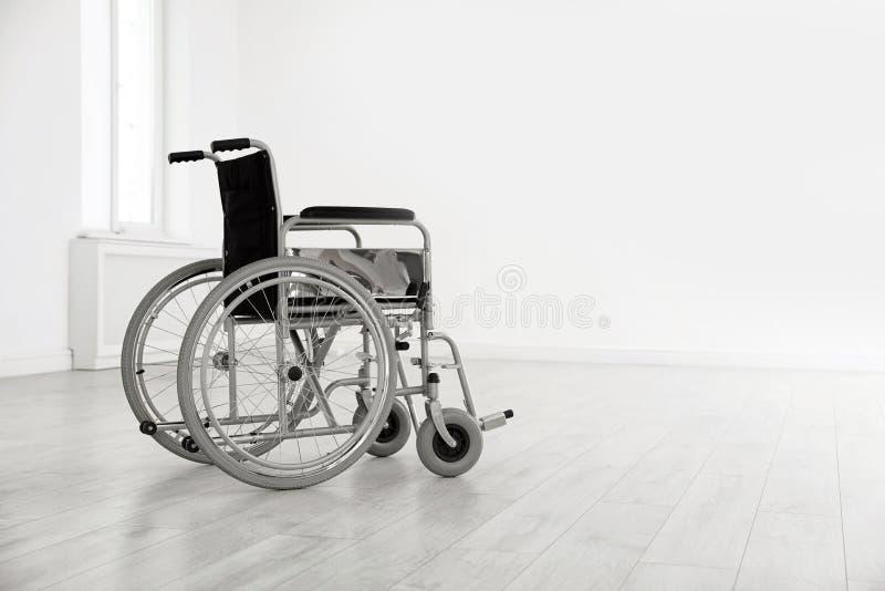 Moderne rolstoel in lege ruimte Medische apparatuur royalty-vrije stock afbeelding