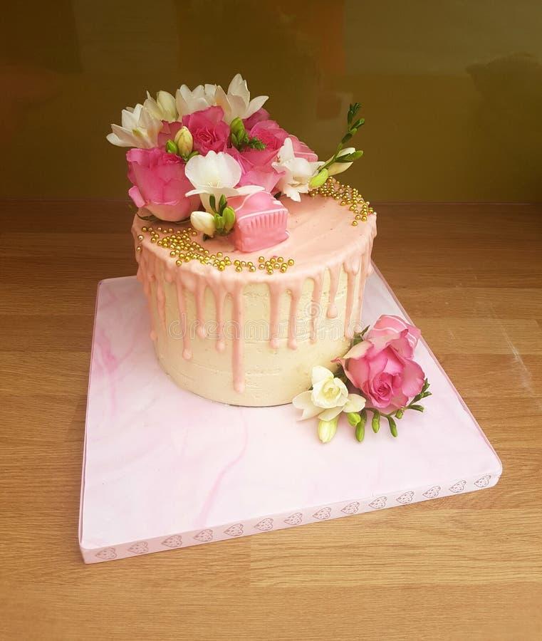 Moderne roze druppelcake met verse bloemen stock afbeeldingen