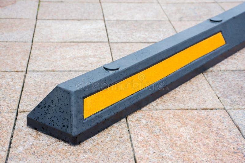 Moderne rubberbarrière voor auto's in de zomerparkeren in de straat stock foto