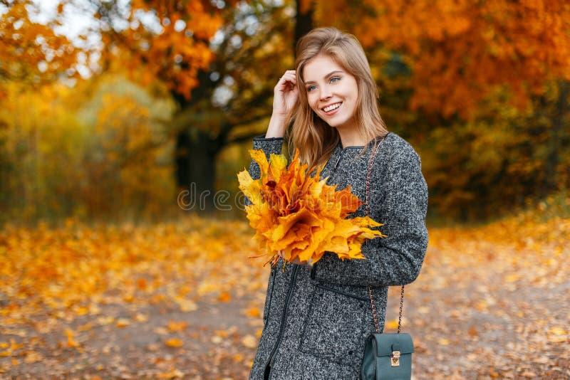 Moderne schöne glückliche Frau in einem modernen Mantel mit einer Handtasche mit Herbstlaubwegen in einem hellen Fallpark lizenzfreies stockbild