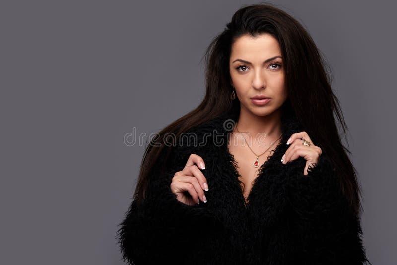Moderne Schönheit im schwarzen Pelzmantel lizenzfreie stockfotos