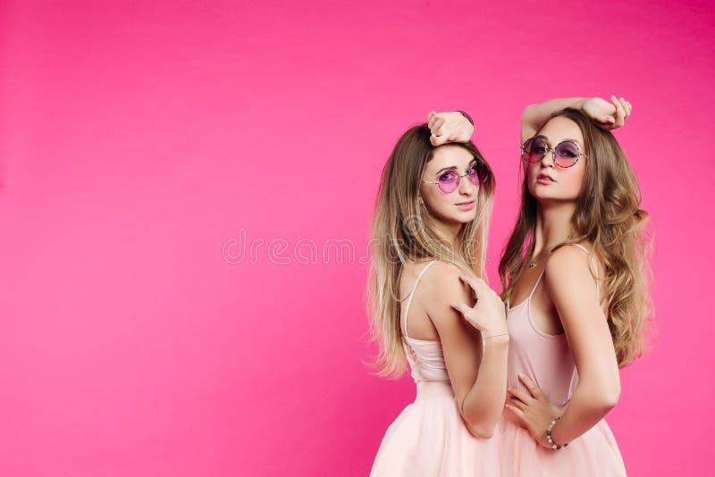 Moderne Schwestern in den rosa Kleidern und in der violetten Sonnenbrille lizenzfreie stockfotos