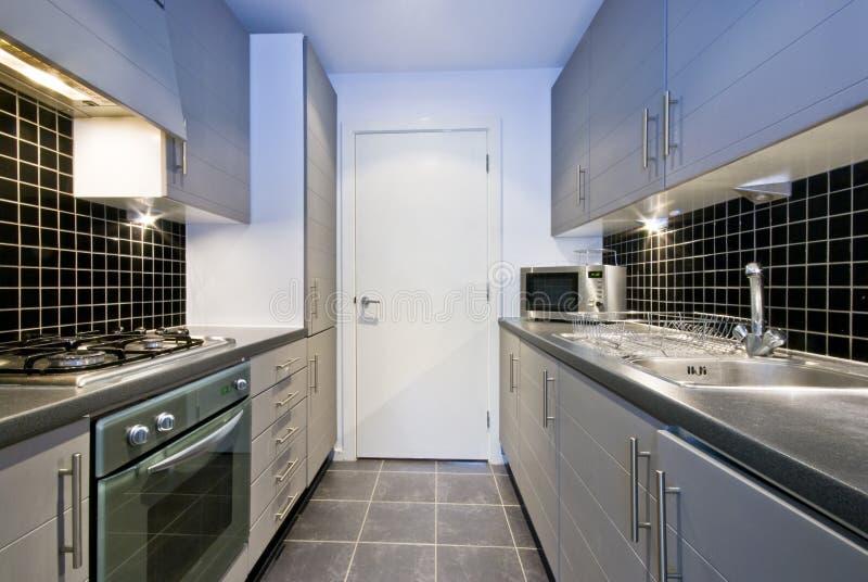 Moderne silberne Küche mit schwarzen Fliesen lizenzfreie stockbilder