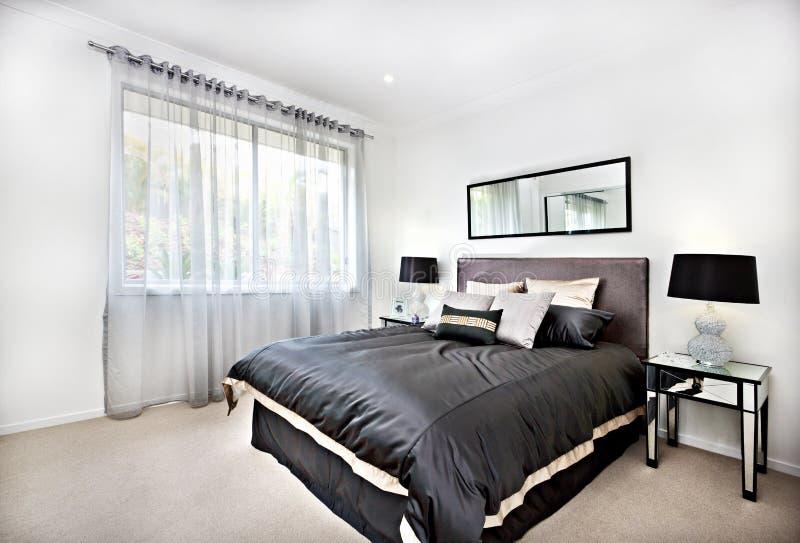 Moderne Slaapkamer Met Zwarte Decoratie En Spiegel Naast Lampen ...
