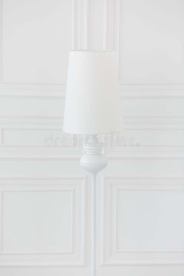 Moderne staande lamp dichtbij witte muren met klassieke afgietsels stock foto's
