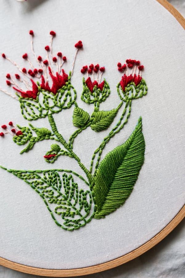 Moderne Stickerei des Bands mit botanischen Motiven auf einem hölzernen Hintergrund lizenzfreie stockbilder