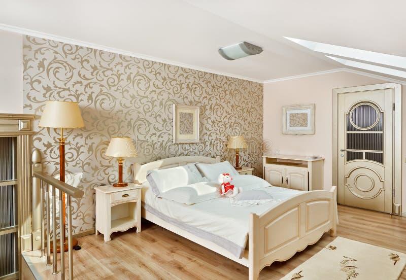 Moderne stijlslaapkamer in de ruimte van de beigeonzolder royalty-vrije stock foto's