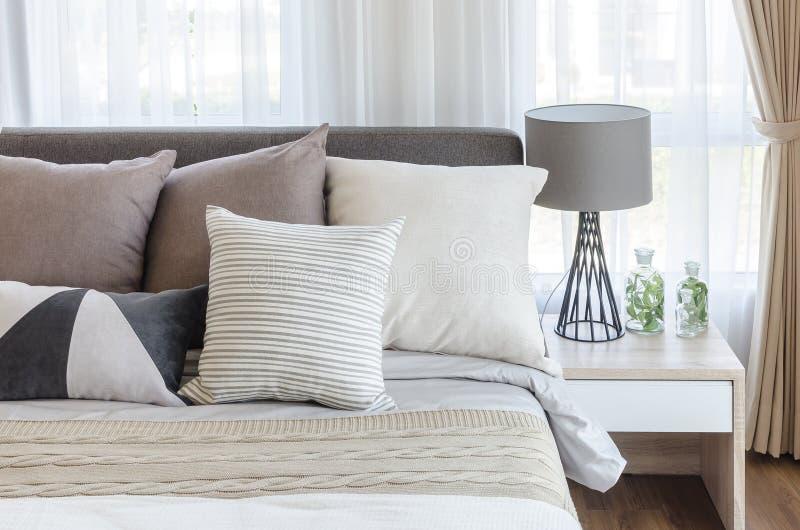 Moderne stijlslaapkamer met hoofdkussens op bed en moderne grijze lamp  stock afbeelding