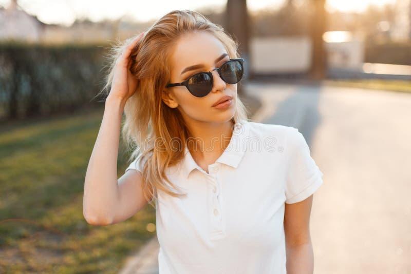 Moderne stilvolle junge Hippie-Frau im modischen weißen Polot-shirt in der schwarzen Sonnenbrille stehen und Aufstellung stockfotografie