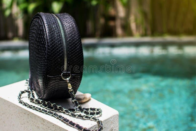 Moderne Tasche der schwarzen Frau Schließen Sie oben von der Luxustasche stilvoller weiblicher snakseskin Pythonschlange draußen  lizenzfreie stockfotos