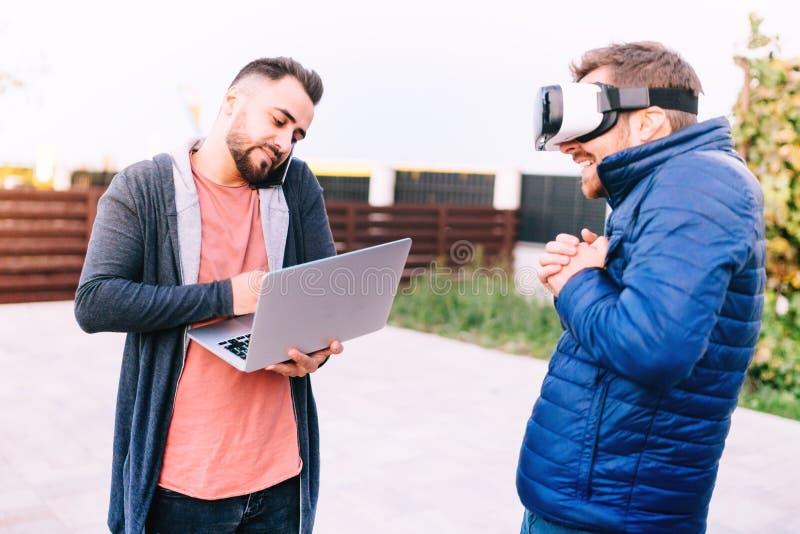 moderne technologieën - moderne levensstijl met twee ontwikkelaars die aan nieuwe apps voor virtuele werkelijkheidsbeschermende b royalty-vrije stock foto