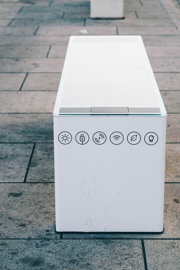 Moderne Technologie Setzen Sie mit Sonnenkollektor- und Handyladegerät in der Ufergegend in Kroatien auf die Bank lizenzfreies stockbild