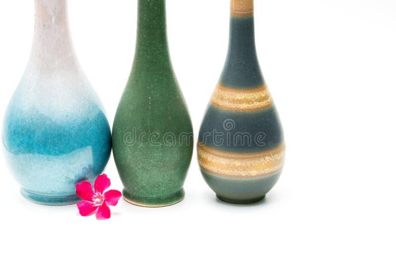 Moderne Tonwarenvasen mit schönen Mustern, rosa Blume vor den Vasen lokalisiert stockbild