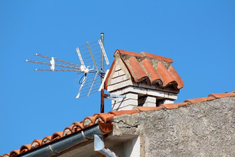 Moderne TV-antenne met drie richtingen opgezet op gedeeltelijk geroeste metaalpijp naast witte baksteenschoorsteen bovenop famili royalty-vrije stock foto