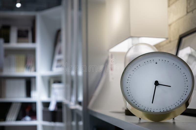 Moderne Uhr im Wohnzimmer mit Buchregalen und -lampe stockbild