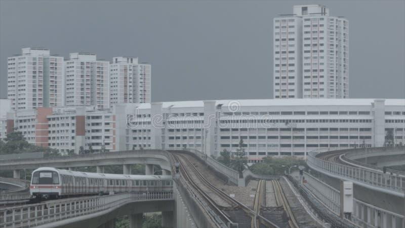 Moderne Untergrundbahn auf einer Eisenbahn in Sinapore auf einem Stadtgebäudehintergrund schuß Schneller Zug Singapurs MASSENMRT stockbild