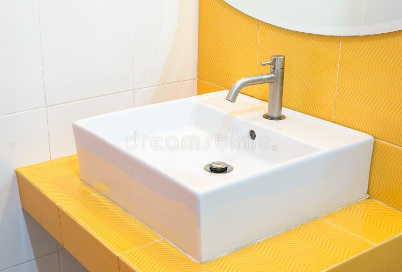 Moderne vierkante gootsteen in de badkamers en de gele muur stock afbeeldingen