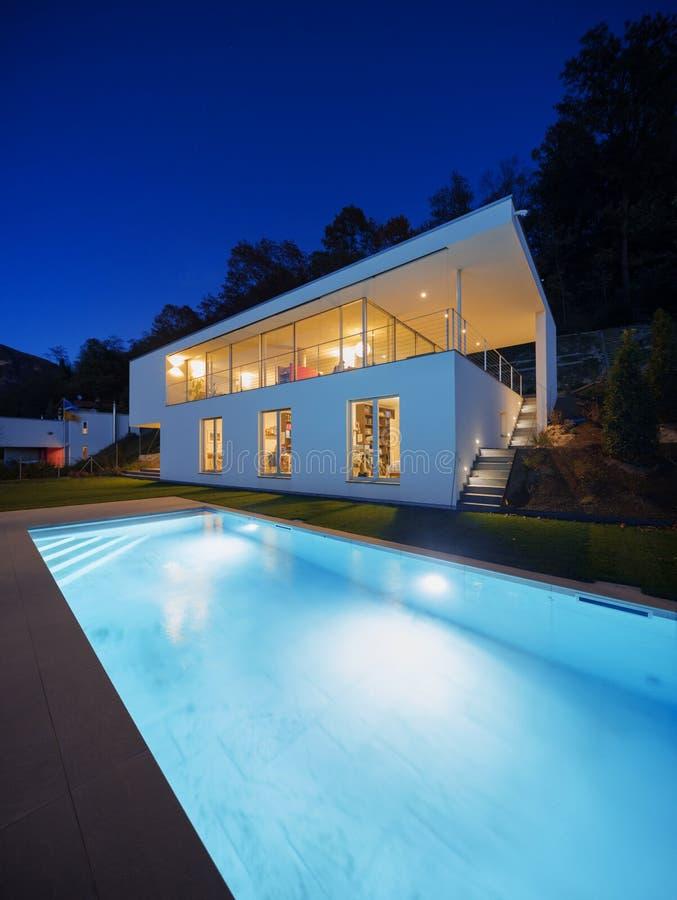 Moderne villa, buitenkant in de nacht, lichten  stock afbeelding
