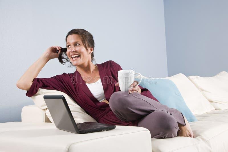 Moderne vrouw die op laag met telefoon, laptop wordt ontspannen stock foto's