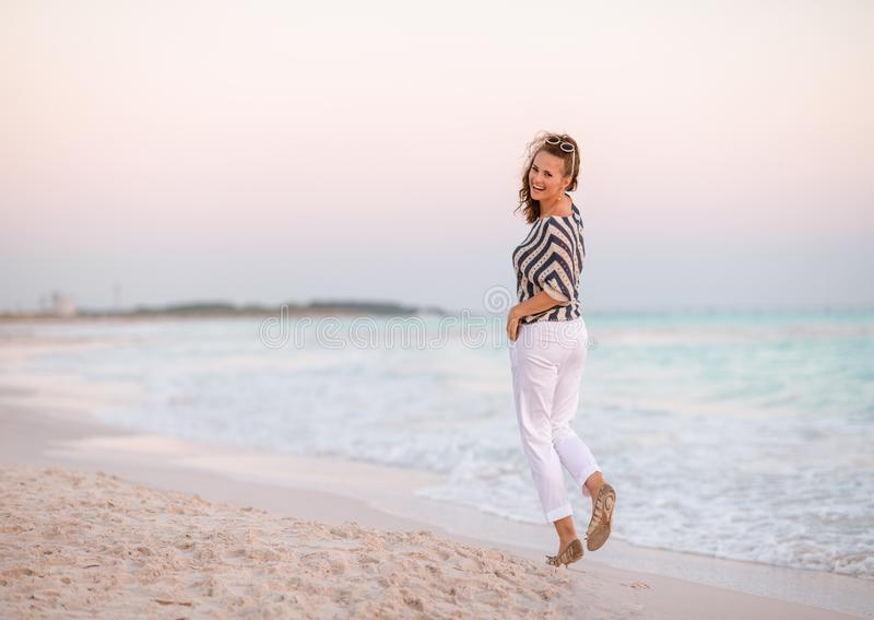 Moderne vrouw op kust bij zonsondergang het lopen stock afbeeldingen