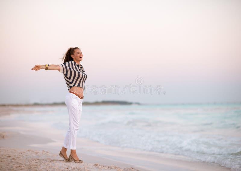 Moderne vrouw op strand bij zich zonsondergang het verheugen royalty-vrije stock afbeelding