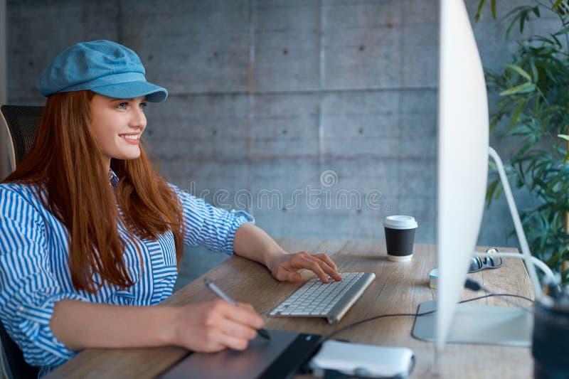Moderne vrouwelijke ontwerper die en op het werk glimlachen werken stock afbeelding