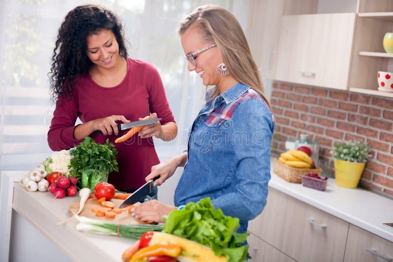 Moderne vrouwen, het koken en pret in de keuken stock foto's