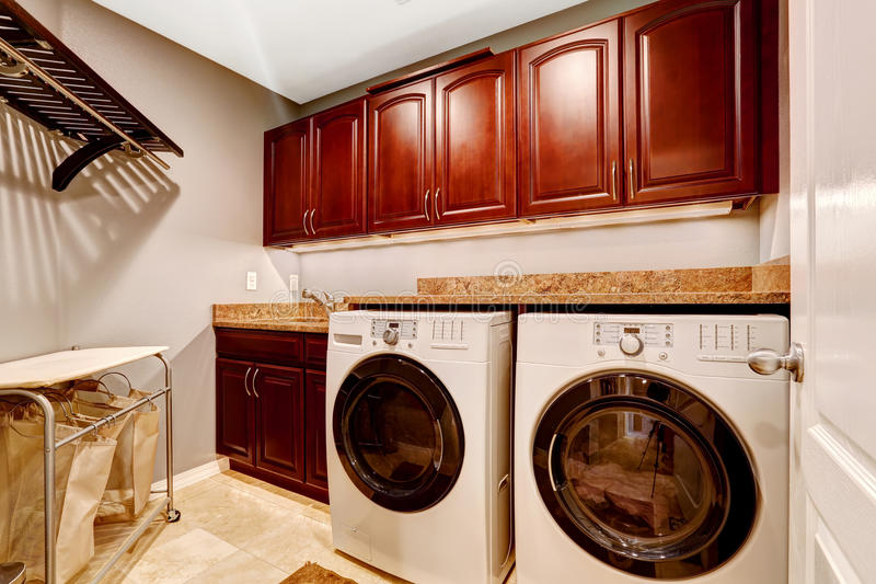 Moderne Waschküche mit Kabinetten und Granitspitze stockbild