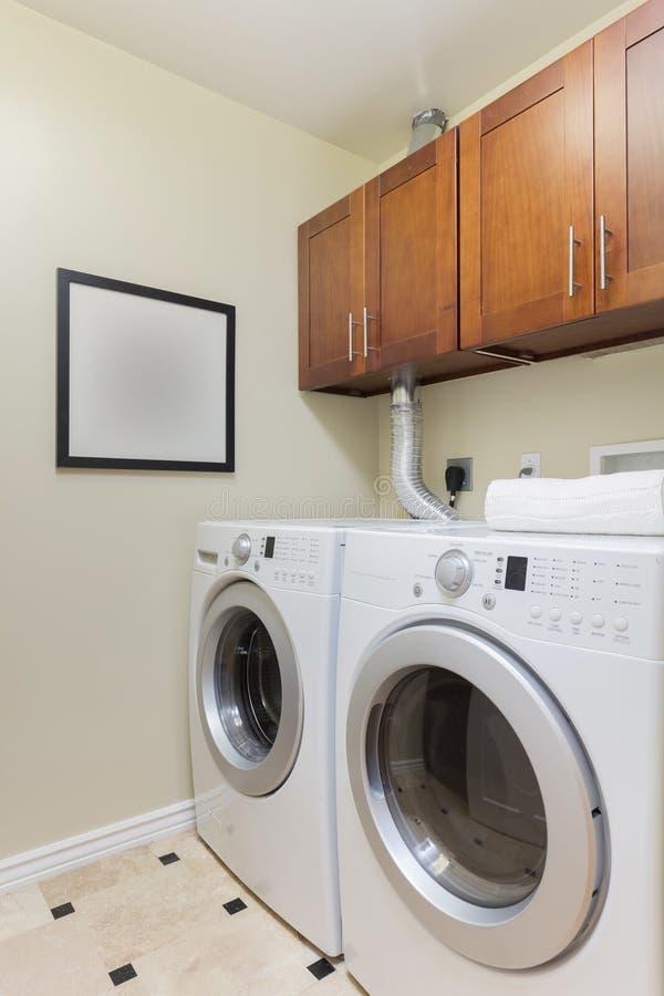 Moderne Waschküche mit modernen Geräten stockbilder