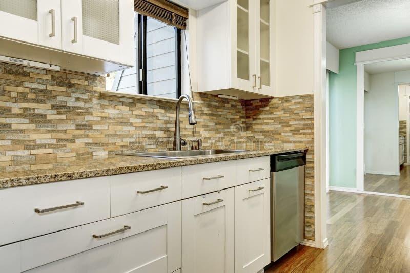 Moderne weiße Kabinette und braune Mosaikrückseite spritzen in der Wohnung stockfotografie
