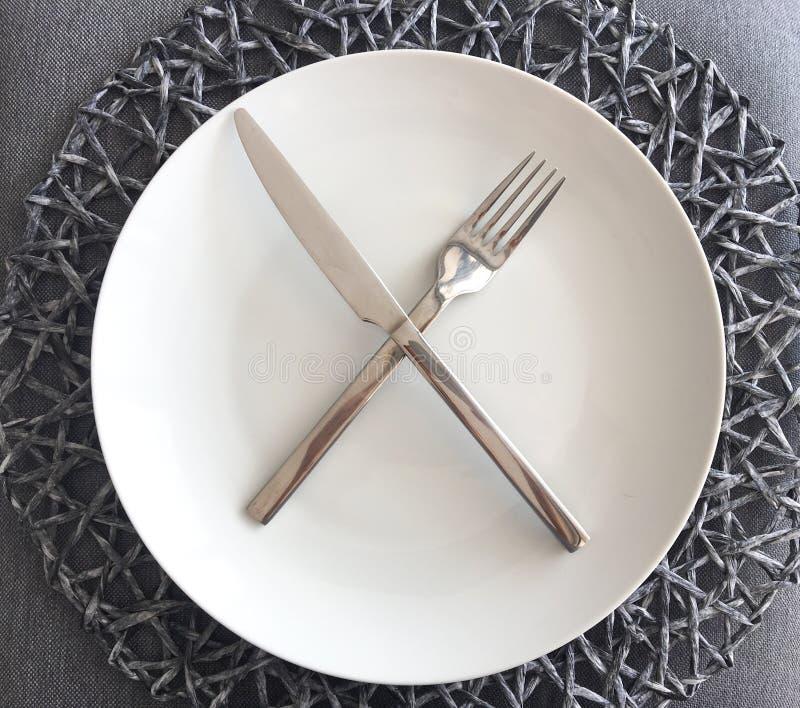 Moderne weiße Platte und Tafelsilber mit Platzmatte stockfotos