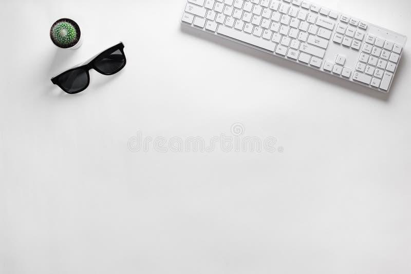 Moderne weiße Schreibtischtabelle mit Tischrechner, Kaktus und Brillen Draufsicht mit Kopienraum, flache Lage stockfotografie