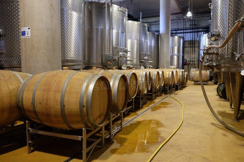 Moderne Weinkellerei mit Aluminiumbehältern und Weinfässern stockbilder