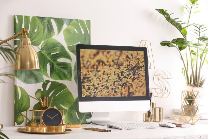 Moderne werkplaats met computer en gouden decor op bureau dichtbij muur Modieuze binnenlands stock fotografie