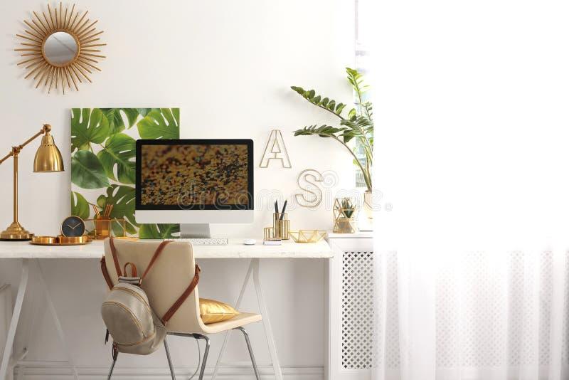 Moderne werkplaats met computer en gouden decor op bureau Modieus binnenlands ontwerp stock foto