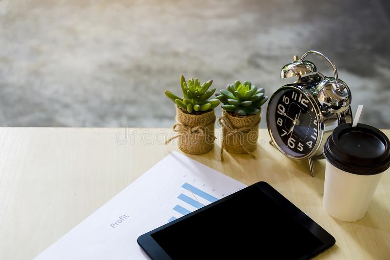 Moderne werkplaats met digitale tablet, de boom van de aardcactus, mobiele telefoon, klok, kop van koffie en documenten met winst royalty-vrije stock afbeelding