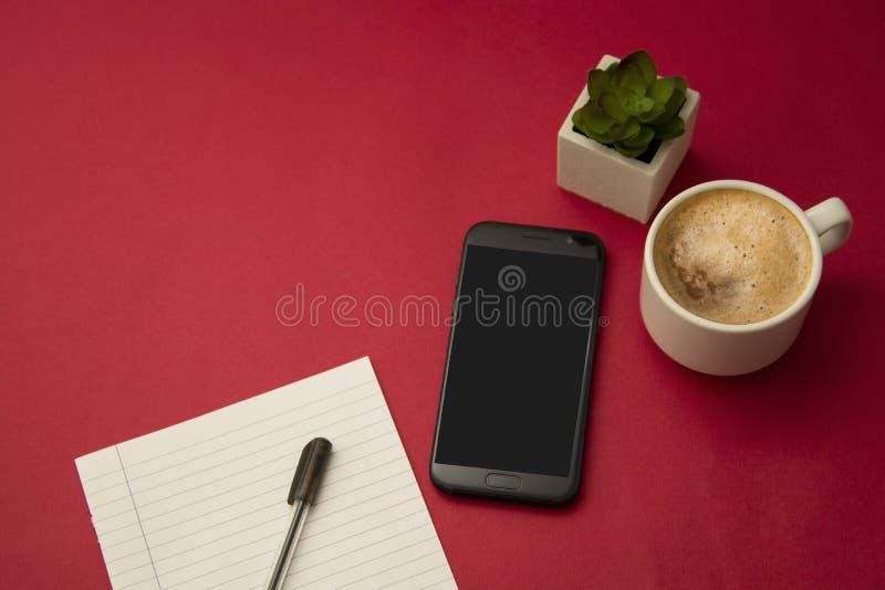 Moderne werkplaats met kop van succulente koffie, smartphone, decoratieve installatie en een pen Rode kleurrijke achtergrond Zake stock afbeelding