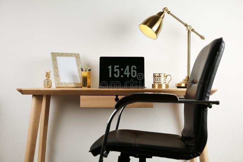 Moderne werkplaats met laptop en gouden decor op bureau dichtbij muur stock afbeeldingen