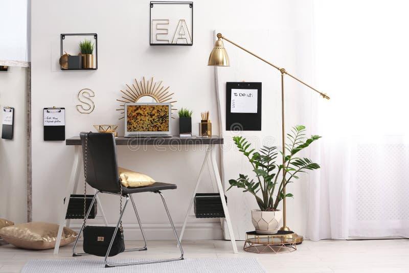 Moderne werkplaats met laptop en gouden decor op bureau dichtbij muur Modieuze binnenlands royalty-vrije stock fotografie