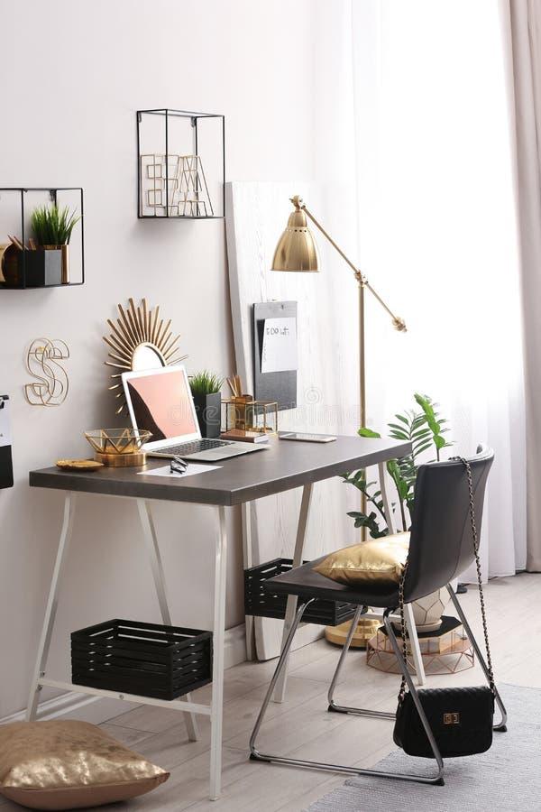 Moderne werkplaats met laptop en gouden decor op bureau Modieus binnenlands ontwerp royalty-vrije stock foto