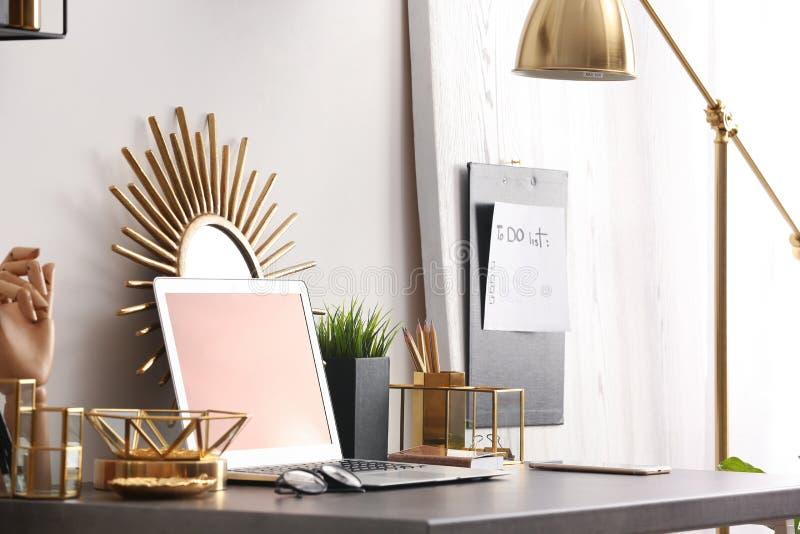 Moderne werkplaats met laptop en gouden decor op bureau Modieus binnenlands ontwerp royalty-vrije stock afbeeldingen